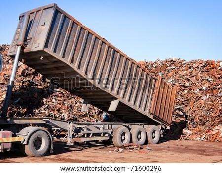 Truck unloading metal rusty scrap in the dock - stock photo
