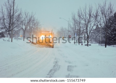 Truck with a snow plow clearing a suburban street - stock photo