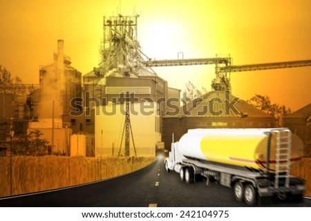Truck with fuel tank in motion blur on the highway into corn dryer silos and beautiful sunset sky in concept of industrial and agriculture - stock photo