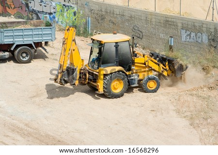 Truck with tractor excavating - stock photo