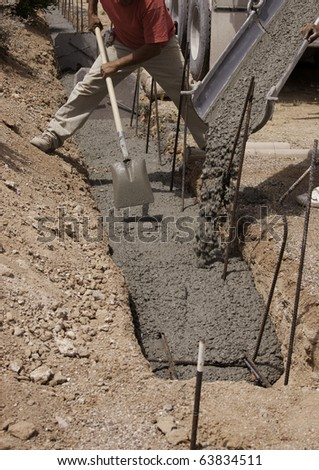 Truck with worker pouring concrete into form. Focus on shovel and hands. - stock photo