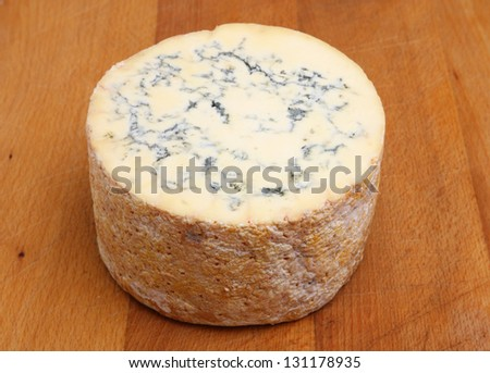 Truckle of Stilton cheese on wooden board.
