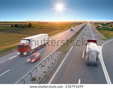 Trucks and car in motion blur on the highway towards the rising sun. Rush hour on the motorway near Belgrade - Serbia. - stock photo