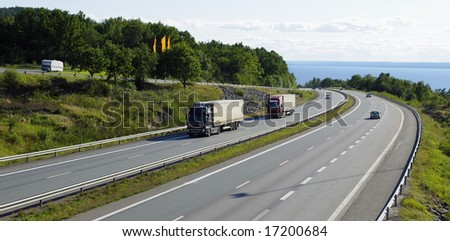 trucks and cars driving on scenic mountain highway, panoramic view. - stock photo
