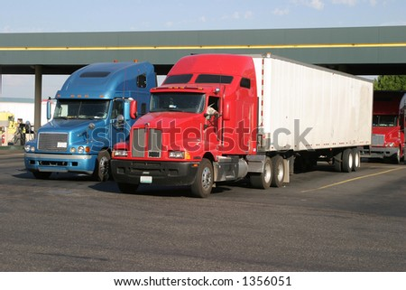 Trucks at a truckstop fueling station - stock photo