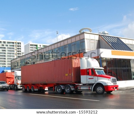 trucks delivering containers into ship yard - stock photo