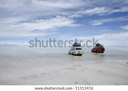 Trucks departing for an adventure over the Bolivian Saltflats - stock photo