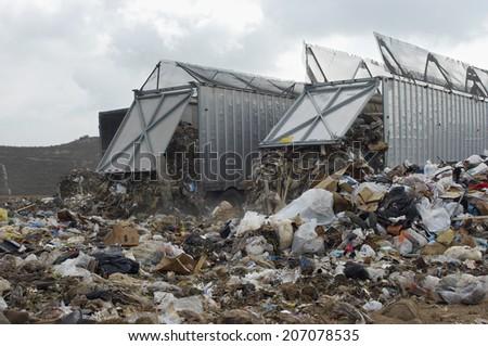 Trucks dumping waste at landfill site - stock photo