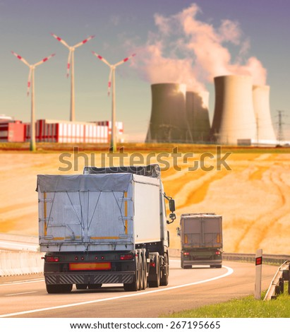 Trucks on the highway in industrial landscape. Shallow DOF and warm filtered look. - stock photo