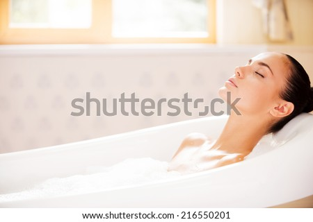 True bliss. Side view of attractive young woman keeping eyes closed while enjoying luxurious bath  - stock photo