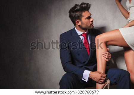 true gentleman is helping his woman to get her shoes on while sitting. sexy couple in studio - stock photo