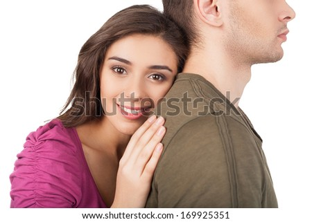 True love. Cheerful young woman hugging her boyfriend and looking at camera while standing isolated on white - stock photo