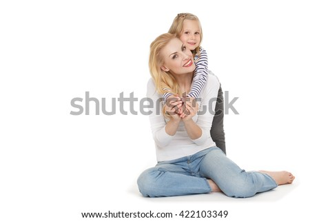 True love. Shot of a little cute girl hugging her cheerful mother from behind looking to the camera cheerfully. - stock photo