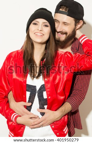 True love.  Studio shot of bearded hipster boyfriend embracing his cheerful girlfriend laughing happily. - stock photo