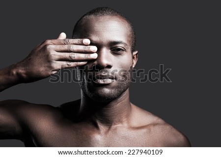 True masculinity. Portrait of young shirtless African man covering one eye with hand and looking at camera while standing against grey background - stock photo