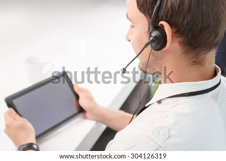 True professional. Top view of busy handsome call center operator holding laptop and doing his job while sitting at the table