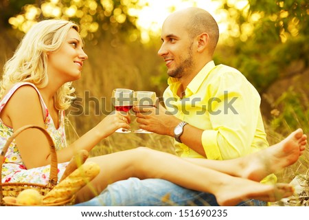 True romance concept. Weekend picnic. Portrait of a young loving couple in trendy casual clothes drinking red wine and enjoying each other. Sunny summer (autumn) day. Outdoor shot - stock photo