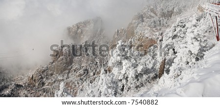True wide panorama of the top of the Sandia Mountains in snow and ice, with the Sandia Tram rising through the clouds of the winter storm. - stock photo