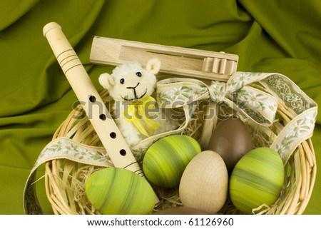 Trug with chocolate, wooden and green painted easter eggs and traditional folklore instruments - rattle and pipe - whistle. - stock photo