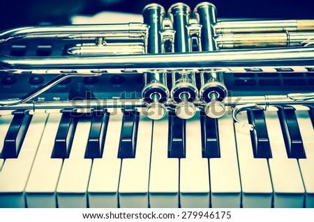 Trumpet on keyboard background - stock photo