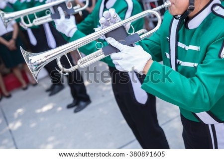 trumpet player in green shirt blowing in marching band - stock photo