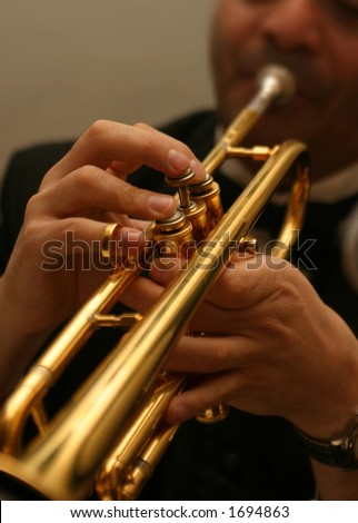 Trumpet player. Narrow focus on fingers.
