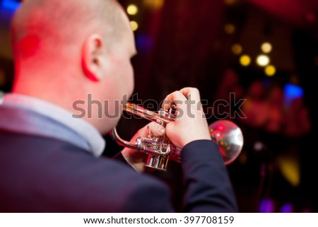 Trumpeter plays the trumpet in a nightclub. - stock photo