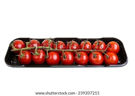 Truss cherry tomatoes on a black carry tray - stock photo