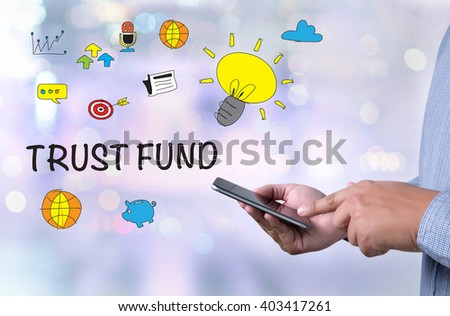 TRUST FUND person holding a smartphone on blurred cityscape background - stock photo