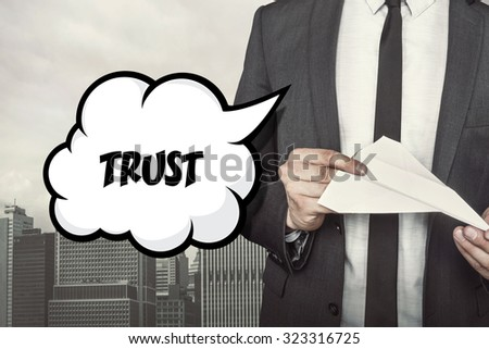 Trust text on speech bubble with businessman holding paper plane in hand on city background - stock photo