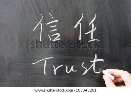 Trust word in Chinese and English written on the chalkboard