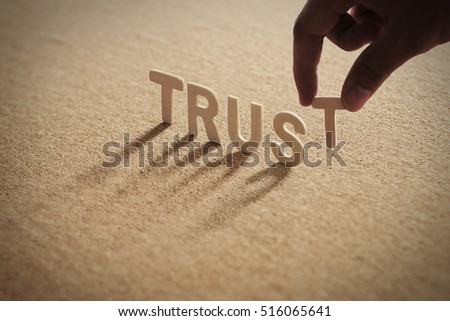 TRUST word of wood alphabet with shadow on cork board,compressed board