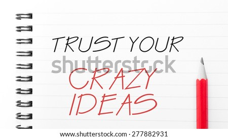 Trust Your Crazy Ideas Text written on notebook page, red pencil on the right. Motivational Concept image