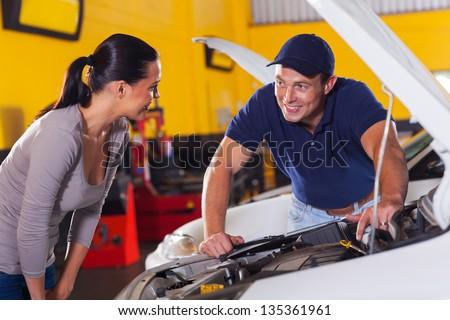 trustworthy auto technician talking to female customer in garage - stock photo