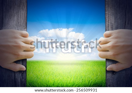 Truth . Hand opening an old wooden door and found Truth word floating over green field and bright blue Sky Sunrise. - stock photo
