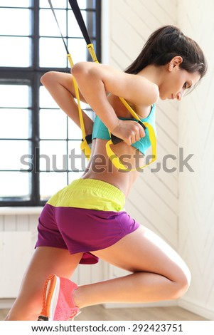 TRX. Beautiful girl in the gym - stock photo
