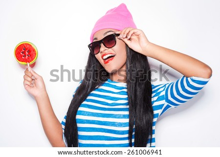 Try my lollipop! Attractive young African woman in funky clothes holding lollipop and smiling while standing against white background - stock photo