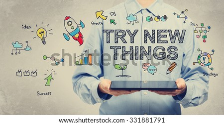 Try New Things concept with young man holding a tablet computer  - stock photo