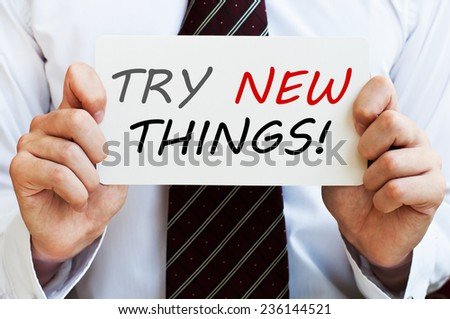 Try New Things! Man holding a card with a message text - stock photo