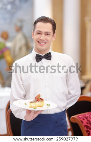 Try our tasty specials. Handsome waiter in uniform stretching out exquisite dessert  on the plate while serving customers in the luxury restaurant - stock photo