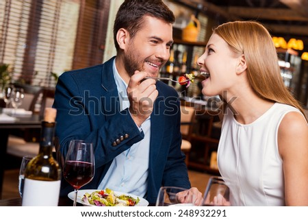 Try this! Beautiful young loving couple enjoying dinner at the restaurant while man feeding his girlfriend with salad - stock photo