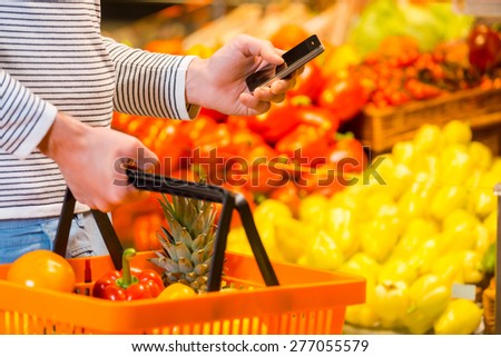 Trying not to forget to buy everything. Close-up of young men holding shopping bag and mobile phone while standing in a food store - stock photo