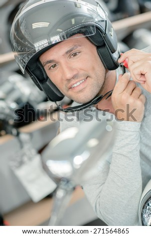 Trying on a motorcycle helmet - stock photo