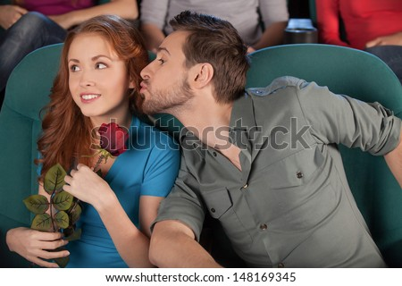 Trying to kiss her. Handsome young men trying to kiss his girlfriend while watching movie at the cinema - stock photo