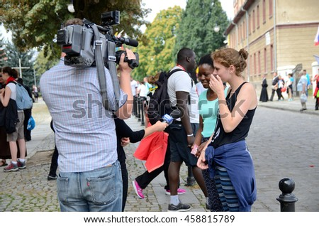 TRZEBNICA, POLAND - JULY 25: World Youth Day, pilgrims interviewed by local TV in front of St. Jadwiga Sanctuary on 25th July 2016 in Trzebnica.