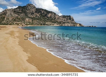 Tsambika (or Tsampika) is one of the most beautiful beaches on Rhodes, Greece. A long, broad beach with fine, golden sand. Very crowded at summer period.  At the far end beach has naturist part.  - stock photo