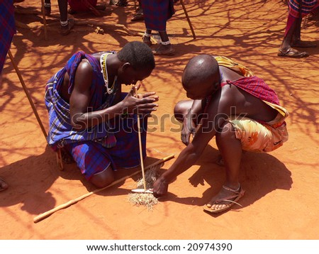 TSAVO EAST, February 15, 2006: Masai warriors showing how they make fire in a tradtiional way to guests visiting their village near Tsavo East. Kenya, on 2006/02/15 - stock photo