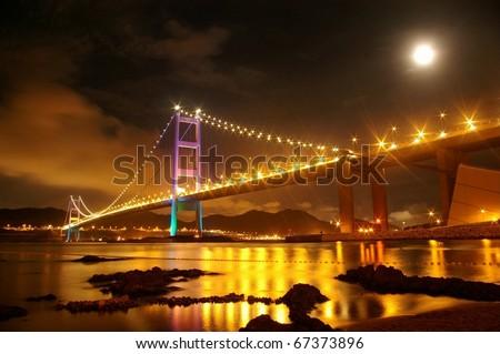 Tsing Ma Bridge with the moon at night - stock photo