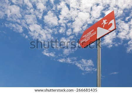 Tsunami evacuation warning bright orange sign with the figure of running man and wave on the blue sky background - stock photo