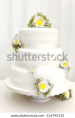 Ttraditional three tier wedding cake with daisy flower decorations. - stock photo
